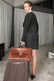 Female chef travelling with suitcase and brief case looking over Stock Photography