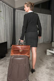 Female chef travelling with suitcase and brief case. Looking over shoulder Stock Photos