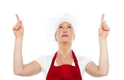 Female chef in uniform pointing upwards. Isolated female chef in uniform pointing upwards against white background Royalty Free Stock Images