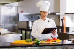 Female chef using digital tablet while cutting vegetables Royalty Free Stock Images