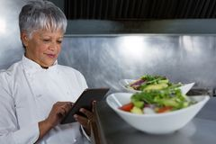Female chef using digital tablet Royalty Free Stock Photography