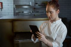 Female chef using digital tablet Royalty Free Stock Photos
