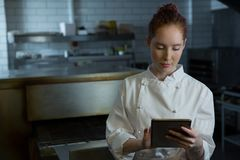 Female chef using digital tablet Stock Images