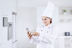 Female chef using a phone in the kitchen. Portrait of young female chef using a mobile phone while standing in the kitchen stock images
