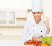 Female chef with vegetables showing ok sign Stock Photo