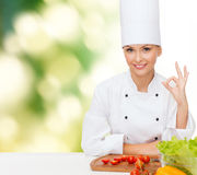 Female chef with vegetables showing ok sign Royalty Free Stock Images
