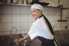 Female chef washing hands in the commercial kitchen. At restaurant Stock Photography