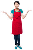 Female chef welcoming you with a smile. Smiling young female chef standing with open palms royalty free stock image