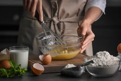 Female chef whisking eggs in glass bowl. On kitchen table Royalty Free Stock Photos