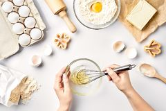 Female chef whisking eggs in glass bowl on kitchen table. Ingredients for the dough: flour, eggs, butter. Top view. Still life. Flat lay Stock Image