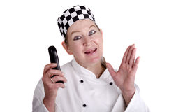 Female chef in work clothes holding a mobile phone Stock Images