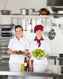 Female Chefs With Dishes At Kitchen Counter. Portrait of happy female chefs with their dishes standing at kitchen counter Stock Image