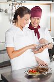 Female Chefs Using Digital Tablet In Kitchen Royalty Free Stock Photography