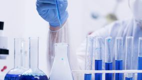 Female chemical scientist in a modern laboratory pouring reagent with pipette from test tubes with blue liquid. Scientist in modern laboratory stock footage