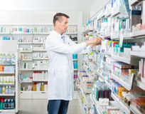 Female Chemist Arranging Products In Pharmacy royalty free stock images