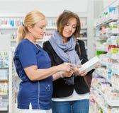 Female Chemist Explaining Product Details To Stock Photo