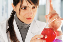 Female chemist with flask filled of red liquid Royalty Free Stock Photo