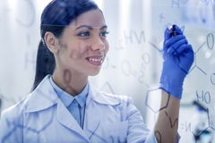 Happy smart woman writing a formula. Female chemist. Happy smart nice woman smiling and writing the formula while working as a chemist Royalty Free Stock Image