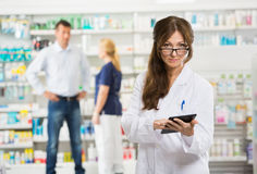 Female Chemist Holding Digital Tablet At Pharmacy Royalty Free Stock Photos