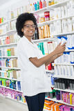 Female Chemist Holding Shampoo Bottle In Pharmacy. Portrait of smiling female chemist holding shampoo bottle in pharmacy Royalty Free Stock Images