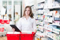 Female Chemist Holding Tablet PC. Portrait of female chemist holding tablet PC standing with basket at drugstore stock photography