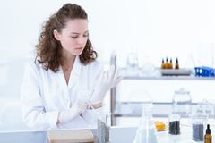 Chemist putting on glove. Female chemist putting on a disposable glove while sitting in a laboratory royalty free stock photo