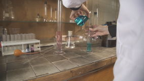 Female chemist working in a chemical laboratory using chemical utensils. She stands for at table whose surface is covered with ceramic tiles, this precaution stock footage