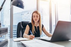 Female chief executive sitting at her desk taking notes in datebook writing with pen and using her computer in modern. Office building Stock Image