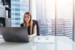 Female chief executive sitting at her desk taking notes in datebook writing with pen and using her computer in modern stock photography