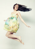 Female in chiffon dress jumping. Young charming female in chiffon dress jumping over grey background Royalty Free Stock Images