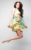 Female in chiffon dress jumping. Young charming female in chiffon dress jumping over grey background Stock Photos