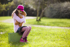 Female child alone sit on a suitcase. Hugging her teddy bear Stock Photos