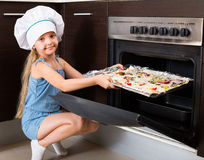 Female child baking pizza at home Royalty Free Stock Image