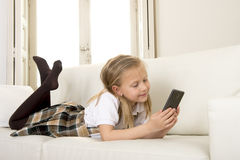Female child with blond hair lying on home sofa using internet app on mobile phone Royalty Free Stock Photography