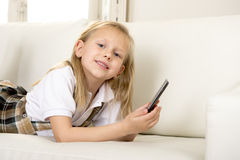 Female child with blond hair lying on home sofa using internet app on mobile phone Stock Photos