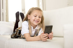 Female child with blond hair in school uniform lying on home sofa couch using internet app on mobile phone Royalty Free Stock Image