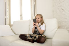Female child with blond hair sitting on couch using internet app on mobile phone Stock Photography