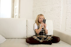 Female child with blond hair sitting on couch using internet app on mobile phone Royalty Free Stock Photo