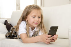 Female child with blond hair sitting on couch using internet app on mobile phone Royalty Free Stock Photos