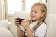 Female child with blond hair sitting on couch using internet app on mobile phone Royalty Free Stock Photography