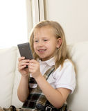 Female child with blond hair sitting on couch using internet app on mobile phone Stock Image