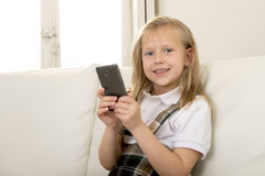 Female child with blond hair sitting on couch using internet app on mobile phone Stock Photos