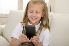 Female child with blond hair sitting on couch using internet app on mobile phone Stock Photo