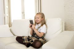 Female child with blond hair sitting on couch using internet app on mobile phone Stock Images