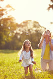 Female child chase soap bubbles. Outside Stock Image