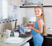 Female child cleaning dishware at home Stock Photo