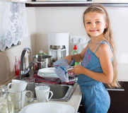 Female child cleaning dishware at home Stock Photography