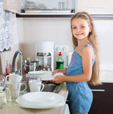 Female child cleaning dishware at home Royalty Free Stock Image