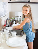 Female child cleaning dishware at home Stock Image