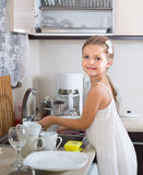 Female child cleaning dishware at home Royalty Free Stock Photography